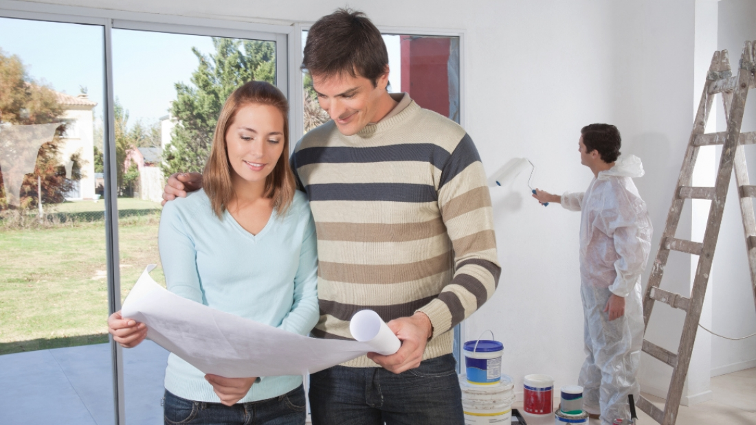 Couple going through house plan while painter in the background